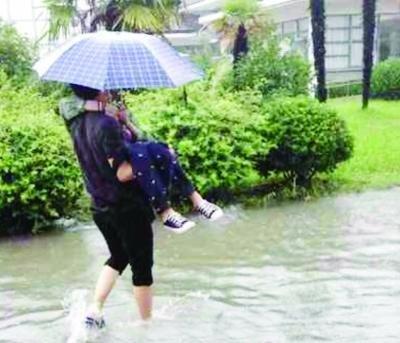 """扬州一高校被淹 瘦弱男生抱妹子过""""河""""上课"""