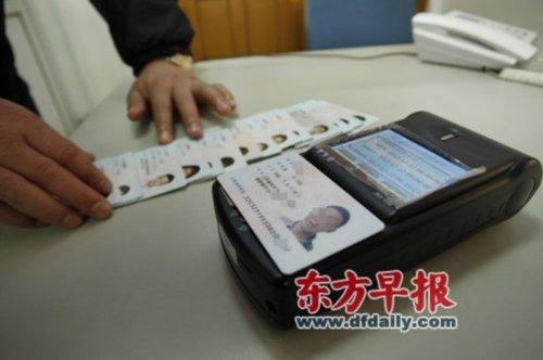 昨天,上海大学工作人员展示用身份证识别仪检测出的无效身份证。早报记者张栋图