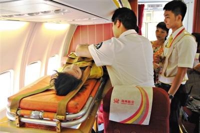 担架上的患病女孩在飞机上被系上安全带