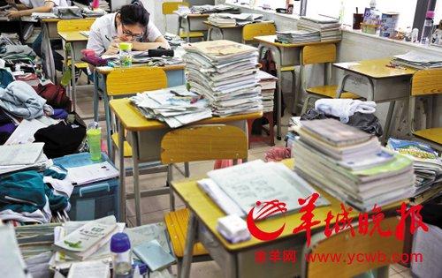 """课间,有学生在专注复习,课室里处处是""""书堆"""""""