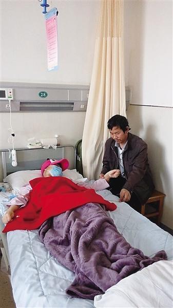 病床前父亲握着女儿的手 西部商报记者 甘菊萍 摄