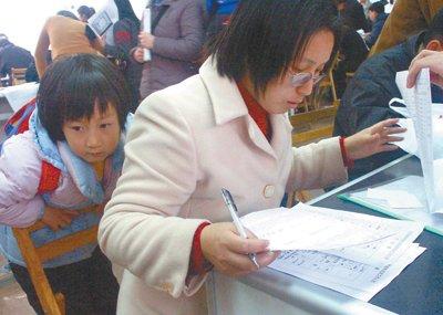 2002年3月,江苏,一位带着孩子的母亲在填写公务员考试报名表。杨晞摄