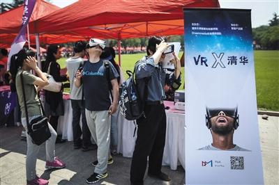 2016年5月21日,清华大礼堂外,家长们向各学院的工作人员咨询招生情况。两位家长在新闻学院前体验VR视频。新京报记者 彭子洋 摄