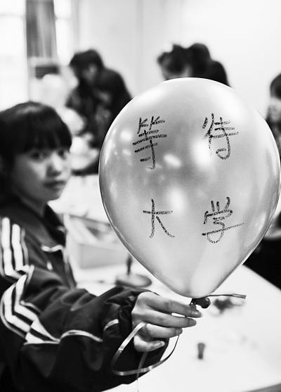 某中学高三考生们在心理老师的带领下,在气球上写下了励志的话语。均为资料图片