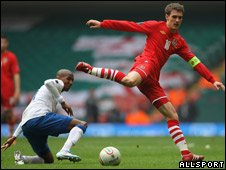 Aaron Ramsey of Wales (red shirt) competes against Ashley Young of England