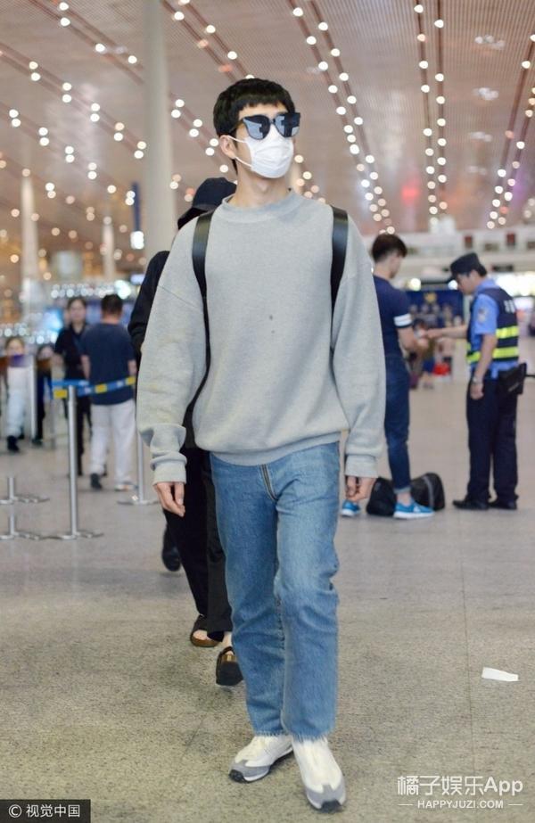 井柏然穿灰色针织衫搭配蓝色直筒牛仔裤,脚踩白色运动鞋,架黑色墨镜