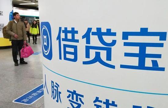 2016年1月8日,北京,一行人从借贷宝logo招牌旁经过。 视觉中国 资料图