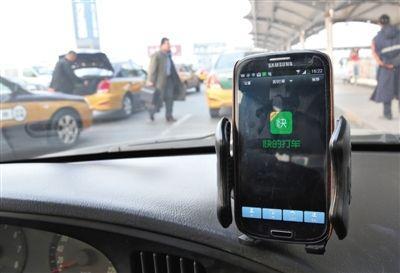 2014年2月17日,首都机场第二航站楼出租下客区,一辆出租上的司机用手机使用打车软件。新京报记者 尹亚飞 摄