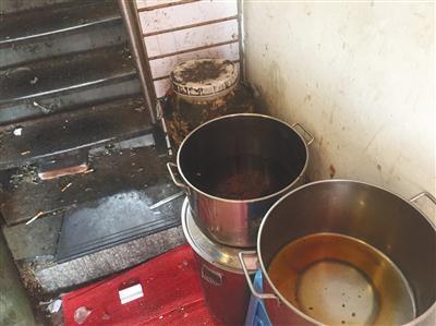 """""""有饭炸鸡""""店铺旁狭窄过道内,潲水桶、盛着油渣的圆桶、面粉等堆在一起,地上散落着烟头、卫生纸、砖块。新京报记者 张越摄"""