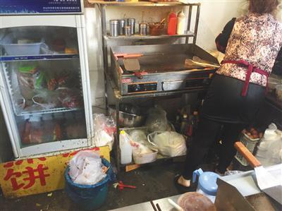 """同时入驻了三家外卖平台的""""台湾手抓饼""""店内,老板娘正在加工食物,店内卫生条件差。后该店被查出无证经营。新京报记者 张越摄"""