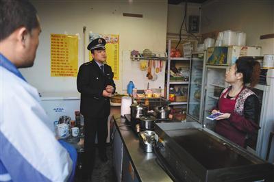 """昨日下午,丰台区食药监局执法人员查处涉嫌违法经营的""""台湾手抓饼""""店,并对经营者进行询问。新京报记者 吴江摄"""