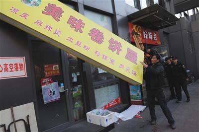 昨日下午,丰台区食药监局执法人员对涉嫌违法经营的店铺招牌进行拆除。新京报记者 吴江摄