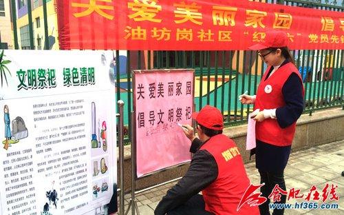 社区老党员在文明祭祀签名展板上签下了自己的名字