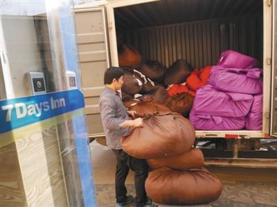 3月20日,7天连锁酒店(北京鸟巢体育场店)门口,丰台区大灰厂村的洗涤厂工人将待洗的布草搬运上车。