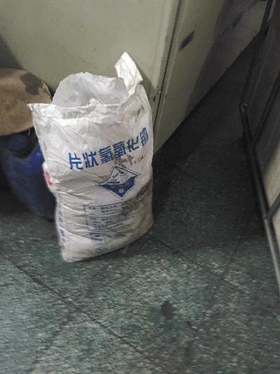 大灰厂村洗涤厂,一袋25公斤的火碱堆在洗衣机旁。