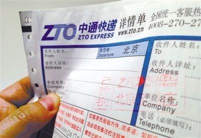 """前日下午,一名中通快递员携带的空白快递单上,盖着""""已验视""""的红章。新京报记者 黄月 摄"""