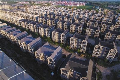 """7月7日,山西省太原市,某房地产开发商近百栋豪华别墅停工多年被杂草包围,从空中望去酷似""""鬼城""""。图/视觉中国"""