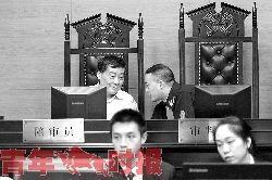宗庆后不时与审判长低头耳语进行交流。
