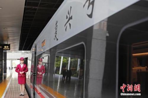 """资料图:4月10日,列车员在""""复兴号""""列车旁迎接旅客的到来。 中新社记者 殷立勤 摄"""