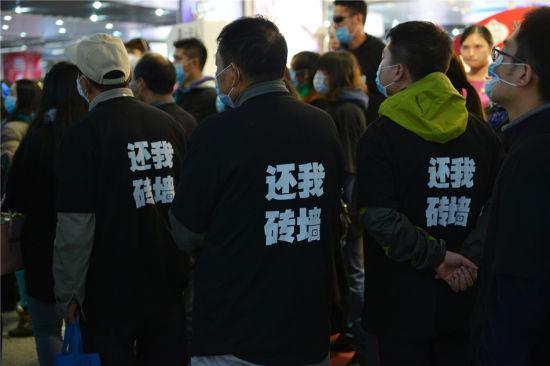 """2015年11月7日下午,几十个面戴口罩身穿黑色T恤的男女老少出现南京新街口地下通道里,胸前印着""""万科坑人""""背后印着""""还我砖墙"""",引起市民的围观。(东方IC)"""