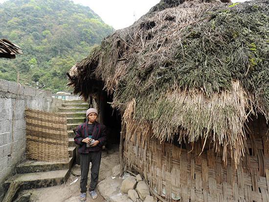 贵州省荔波县瑶山乡巴平村弄哄组,66岁的村民蒙二妹站在自家居住的房屋前,她和儿子兰金华住的茅草房已有几十年历史,是用树枝、竹片拼成的(3月22日摄)。 新华社记者 陶亮 摄