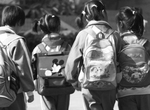 中国小学生背着沉重的大书包上学.图片