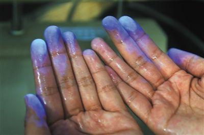 手指沾上荧光剂后,即使是用清水清洗也还有明显的荧光蓝。