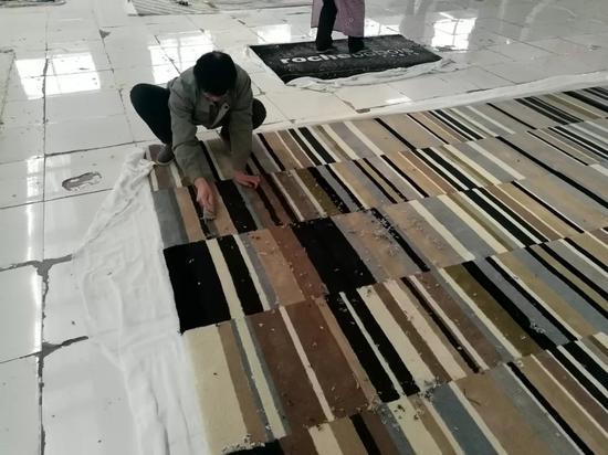 挂胶工人们需要把毯子清理干净后,用刷子把胶体一道一道涂抹在毯背上,这种技术要掌握'火候',不能厚薄不均,也不能涂出布边,更不能有漏胶。这些机器可能连碰都碰不了。