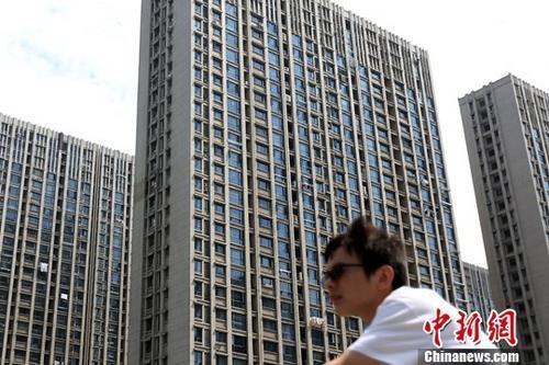资料图:市民从南京一处楼盘前经过。中新社记者 泱波 摄