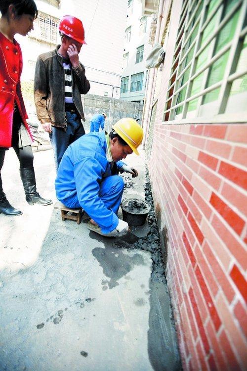 泉8栋楼房地面沉降追踪:施工方水泥修补裂缝