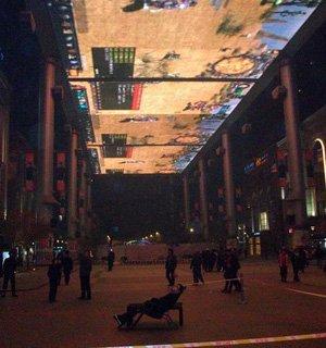 玩家在世贸天阶巨幕下玩网游