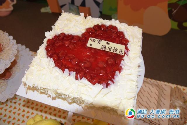 两公婆为女儿准备的满月蛋糕,都是红色心型图案,一家三口充满