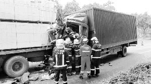 广州两货车相撞两人被困 这时车开始漏油