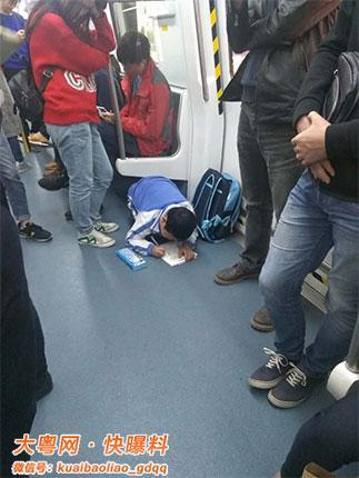 深圳娃趴地铁门边写作业 红衣女子全程看着