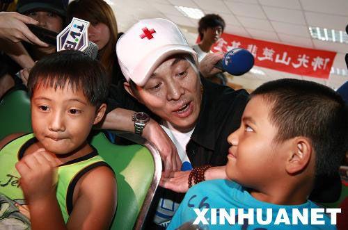 8月15日,李连杰(中)在台湾高雄县旗山镇灾民收容所,与高山族小朋友共唱《我们是一家人》。