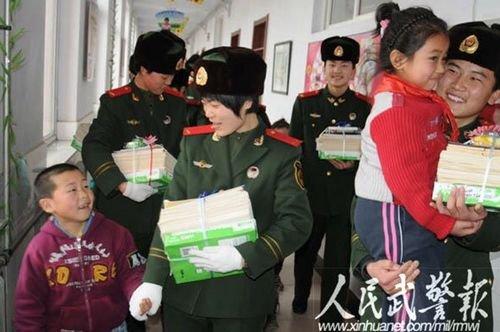 官兵们给孩子们送来学习用品,大手小手紧紧握在一起。