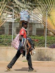 头顶大摞报纸、手臂搭着大捧皮带的小贩。