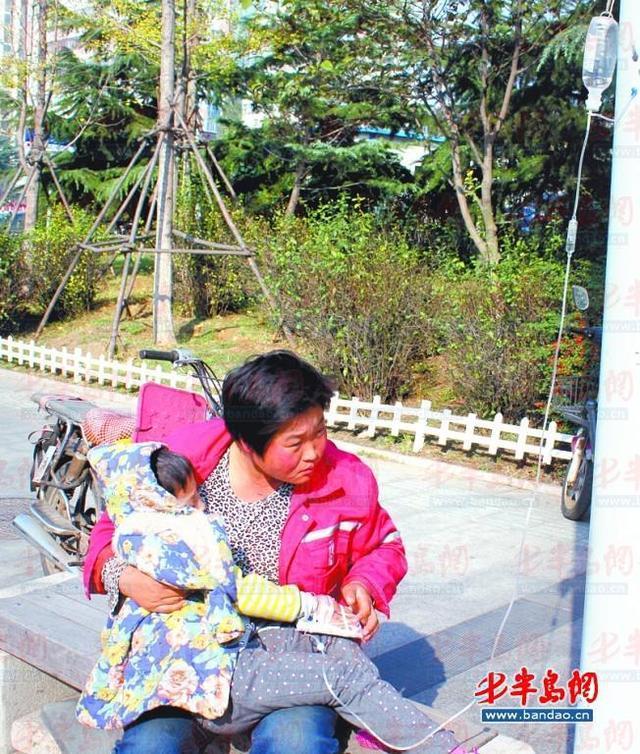 青岛女环卫工抱女儿路边打吊瓶:想保住这份工作