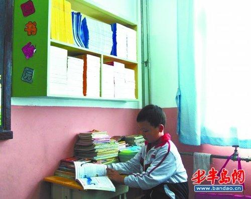 一位小学生正在图书角读书.