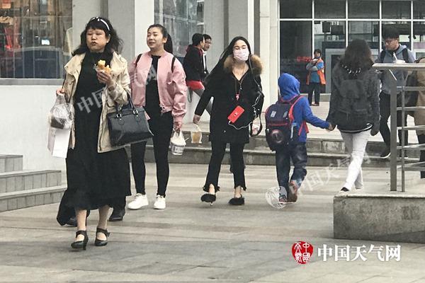 昨晨武汉天气阴冷,市民穿着厚秋装出行。(图/李梦蓉)