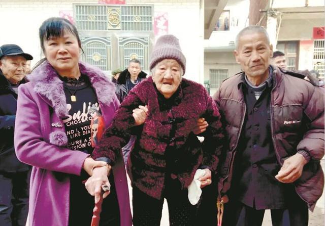 图为:朱花容(左一)扶着刘婆婆参加百岁生日宴