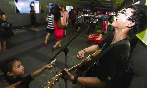 武汉帅气街头歌手受瞩 用爱情励志音乐激励路