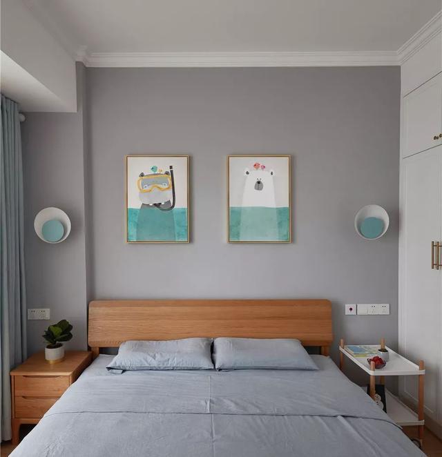 ▲灰色布艺床品搭配原木家具,加之蓝色调的可爱风的挂画和壁灯,
