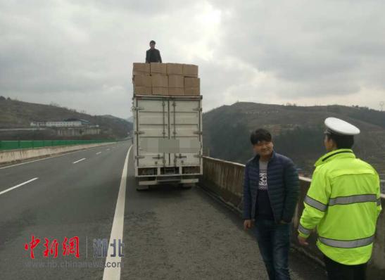 十堰高速上惊现一男子坐车顶 原是为加固货物