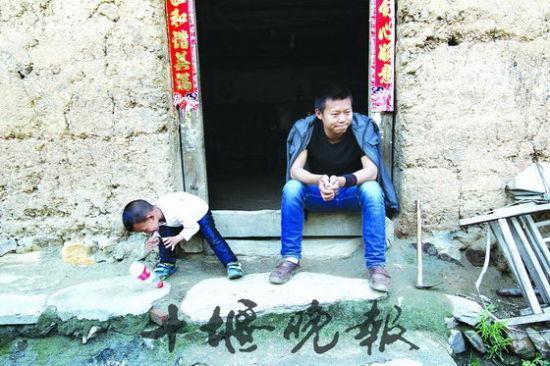 郝富强坐在门口一筹莫展,4岁的儿子郝俊熙拿一个空瓶子当玩具。
