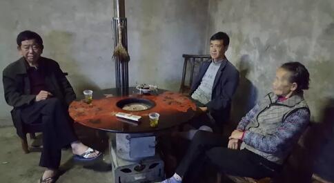 △华孝友带着伤脚入户走访(左一)