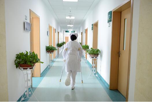 90后护士打石膏架双拐为患者治疗 患者家属拍感人一幕刷爆朋友圈