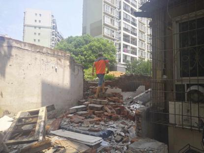 武汉一段围墙被推倒 小孩上学踩着残垣进出