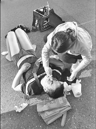 外卖小哥骑车与公交相撞倒地 过路医生好心救护
