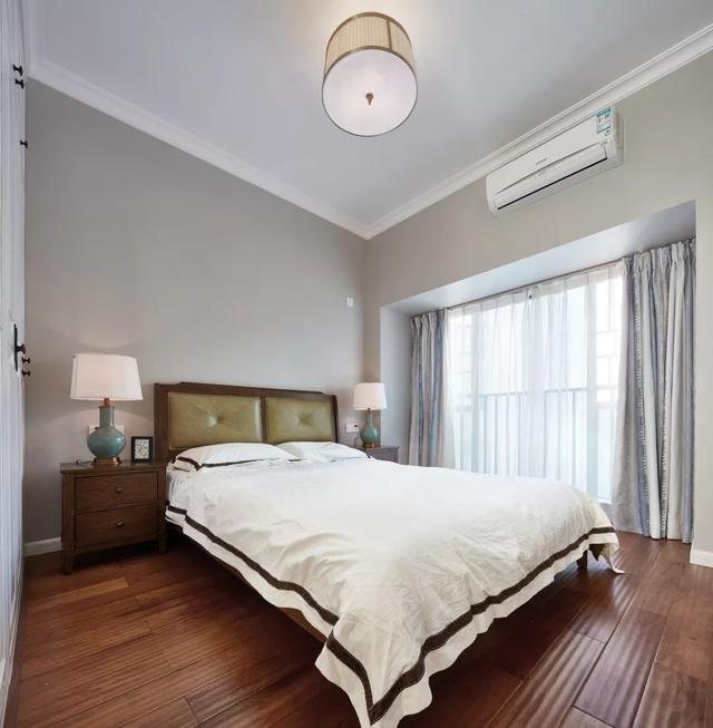 卧室的天花板四周装上石膏线,深色木地板,与暖灰色墙面,搭配白色